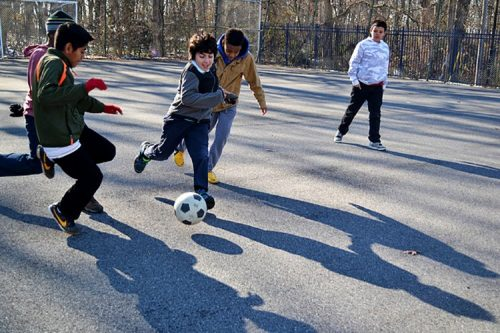 boys playing soccer at recess