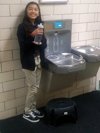 Girl Filling Water Bottle at Fountain