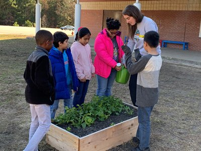 Kids with Teacher Watering Planter Box