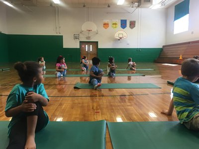 Kids Stretching in Gymnasium