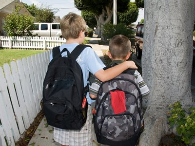 Two kids walking with backpacks.